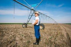 Agricoltore sugli impianti di irrigazione Immagine Stock Libera da Diritti