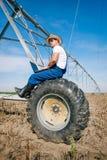 Agricoltore sugli impianti di irrigazione Immagine Stock