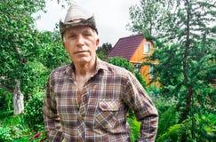 Agricoltore sui precedenti di un giardino di estate Immagine Stock