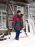 Agricoltore sui precedenti di una casa di secolo Villaggio di Altai, Russ Fotografia Stock Libera da Diritti