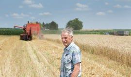Agricoltore sul campo con il harbester dell'associazione Fotografie Stock Libere da Diritti