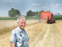 Agricoltore sul campo con il harbester dell'associazione Fotografia Stock Libera da Diritti