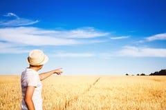 Agricoltore sul campo delle orecchie mature una rappresentazione un dito nella distanza Fotografie Stock Libere da Diritti