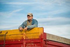Agricoltore sul rimorchio di trattore Fotografia Stock