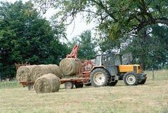 Agricoltore sul suo trattore che prende i mucchi di fieno in Savoia, Francia Immagini Stock Libere da Diritti