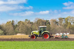 Agricoltore sul trattore che ara suolo sabbioso nella stagione primaverile Fotografie Stock