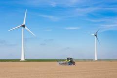 Agricoltore sulla semina del trattore nel suolo vicino alla diga ed ai mulini a vento Immagine Stock Libera da Diritti