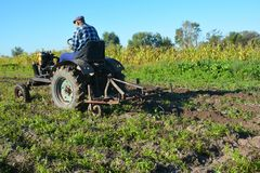 Agricoltore sulla vecchia aratura fatta a mano del trattore Trattore dell'agricoltore Fotografia Stock