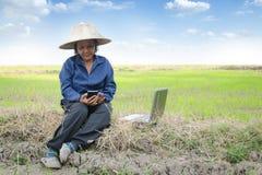 Agricoltore tailandese asiatico che utilizza smartphone e computer portatile nel ri Fotografie Stock