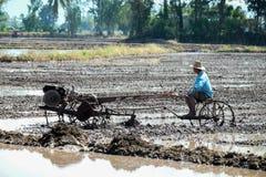 Agricoltore tailandese che utilizza il trattore dell'attrezzo nel giacimento del riso Fotografie Stock Libere da Diritti