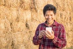 Agricoltore tailandese che utilizza smartphone in un'azienda agricola Fotografia Stock Libera da Diritti