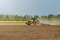 Agricoltore in trattore che prepara il coltivatore di semenzaio della terra agricoltura Immagine Stock Libera da Diritti
