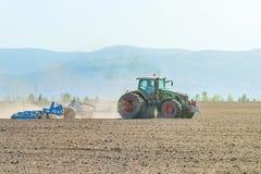 Agricoltore in trattore che prepara il coltivatore di semenzaio della terra agricoltura Immagine Stock