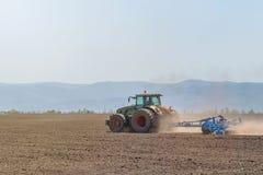 Agricoltore in trattore che prepara il coltivatore di semenzaio della terra agricoltura Fotografia Stock