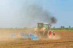 Agricoltore in trattore che prepara il coltivatore di semenzaio della terra agricoltura Fotografie Stock