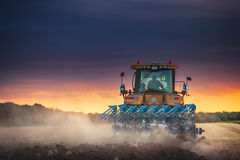 Agricoltore in trattore che prepara terra con il coltivatore Immagine Stock