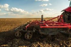 Agricoltore in trattore che prepara terra con il coltivatore di semenzaio Fotografia Stock Libera da Diritti