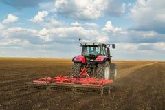 Agricoltore in trattore che prepara terra con il coltivatore di semenzaio Immagine Stock Libera da Diritti