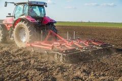 Agricoltore in trattore che prepara terra con il coltivatore di semenzaio Fotografie Stock