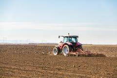Agricoltore in trattore che prepara terra con il coltivatore di semenzaio Immagine Stock