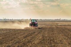 Agricoltore in trattore che prepara terra con il coltivatore di semenzaio come componente delle attività pre di semina nella stag Immagine Stock Libera da Diritti