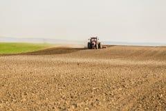 Agricoltore in trattore che prepara terra con il coltivatore di semenzaio come componente delle attività pre di semina nella stag Immagini Stock