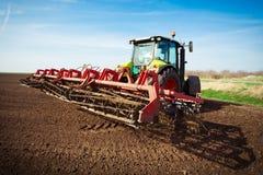 Agricoltore in trattore che prepara terra con il coltivatore di semenzaio in conte Immagine Stock