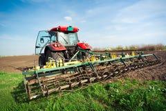 Agricoltore in trattore che prepara terra con il coltivatore di semenzaio in conte Fotografie Stock