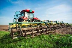 Agricoltore in trattore che prepara terra con il coltivatore di semenzaio in conte Immagini Stock