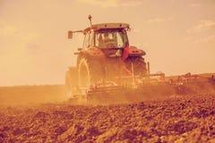 Agricoltore in trattore che prepara terra con il coltivatore di semenzaio Immagine filtrata Immagine Stock Libera da Diritti