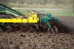 Agricoltore in trattore che prepara terra con il coltivatore di semenzaio in molla in anticipo Immagine Stock Libera da Diritti