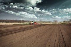 Agricoltore in trattore che prepara terra con il coltivatore di semenzaio in molla in anticipo Fotografie Stock Libere da Diritti