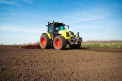 Agricoltore in trattore che prepara terra con il coltivatore di semenzaio in molla in anticipo Fotografia Stock