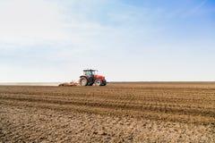 Agricoltore in trattore che prepara terra con il cultivatorFarmer di semenzaio in trattore che prepara terra con il coltivatore d Immagine Stock Libera da Diritti