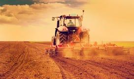 Agricoltore in trattore che prepara terra per seminare Fotografia Stock Libera da Diritti