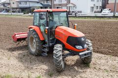 Agricoltore in trattore che prepara terra per seminare Immagini Stock