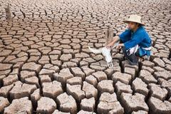 Agricoltore triste che si siede dal suo cranio della testa del bufalo sulla terra del deserto Immagini Stock Libere da Diritti