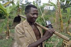 Agricoltore ugandese del ritratto con la zappa, radio portatile Immagini Stock