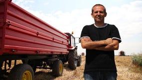 Agricoltore in un giacimento di grano durante il raccolto Fotografia Stock