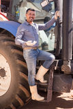 Agricoltore vicino al grande trattore delle ruote Fotografie Stock Libere da Diritti