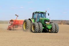 Agricoltore Working il campo con John Deere Tractor e la seminatrice Immagine Stock