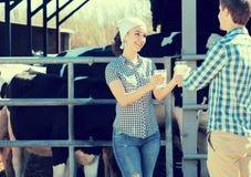 Agricoltori allegri della ragazza e del ragazzo che stanno con nel capannone della mucca Fotografia Stock