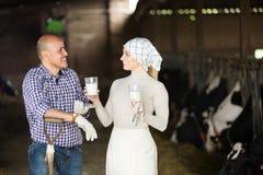 Agricoltori che chiacchierano e che godono del latte Fotografia Stock