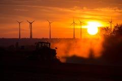 Agricoltori che lavorano con un trattore sul campo al tramonto con i generatori eolici nei precedenti Fotografie Stock Libere da Diritti