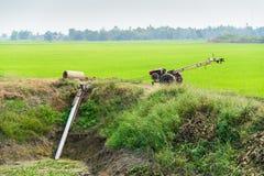 Agricoltori che pompano acqua alle risaie del gelsomino con il vecchio trattore Fotografie Stock Libere da Diritti