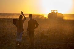 Agricoltori con il computer portatile nel campo al tramonto Fotografia Stock Libera da Diritti