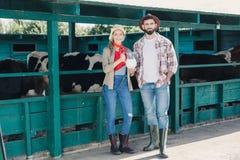 Agricoltori con latte fresco alla stalla Fotografie Stock