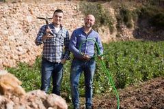 Agricoltori con le vanghe alla piantagione Fotografie Stock Libere da Diritti