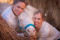 agricoltori delle ragazze con un cavallino bianco-maned fotografia stock