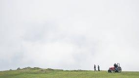 Agricoltori e un trattore sulla cima di una collina Immagini Stock